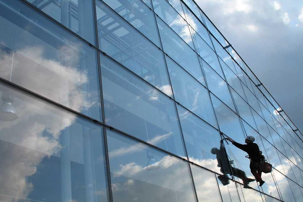 Промышленный альпинист моет окна