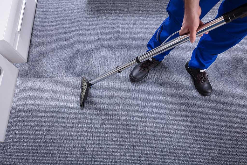 Мужчина моет ковровое покрытие
